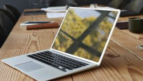 Reflection of window on laptop at conference table